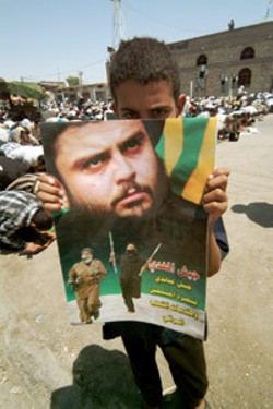 LORNA TYCHOSTUP - A young boy holds a poster of Moqtada Al-Sadr, who has become the symbol of Iraq's Rebellion against the American Occupation.