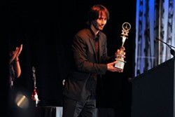 Actor Keanu Reeves accepts an award for Excellence in Acting Award. - DAVID CUNNINGHAM