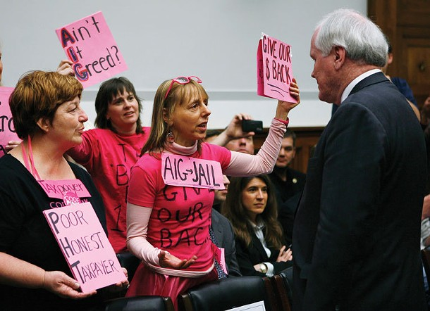 """AIG CEO Edward Liddy interacts with protestors from the group """"Code Pink"""" as he arrives to testify before the House Financial Services Subcommittee on Capital Markets, Insurance, and Government Sponsored Enterprises on Capitol Hill in Washington, dc, on March 18, 2009."""