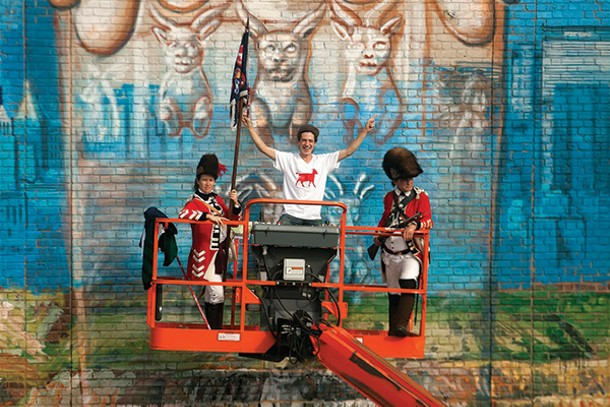 Artist Gaia is flanked by a pair of Redcoats re-enacting the Burning of Kingston on October 5 in front of his mural on Crown Street for the O+ Festival. - ANDY MILFORD