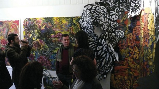 """Artist Paul Spaldone (wearing scarf) being interviewed at the opening of his one-man show """"The Monstrous Among Us: Folly, Excess, Collapse"""" at Team Love Raven House Gallery in New Paltz on February 11. - NATE KRENKEL"""
