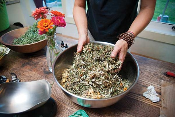 Dana Eudy mixing calendula, comfrey, oats, and plantain that will be infused in oil to make a healing salve.