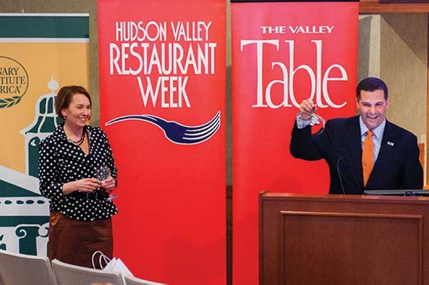 Dutchess County Executive Marc Molinaro rings a bell declaring the opening of the seventh annual Hudson Valley Restaurant Week while Valley Table publisher Janet Crawshaw looks on at the Culinary Institute of America in Hyde Park on February