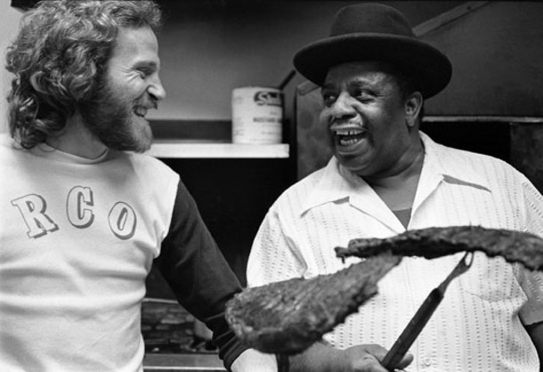 """Eddy Cotton's Fabulous Ribs, Los Angeles, California, April 1975 - """"Levon took the whole crew out to eat at this barbeque place. The menu was great: Eddy's Own Dippin' Sauce, chitlins, greens, corn bread…That's Eddy himself in the kitchen shots. The customers were watching me take photos and everyone was making jokes. Right at this moment Levon turned toward the camera and gave me that 'You getting this?' look."""""""