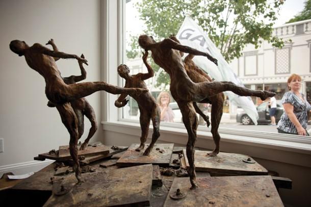 """Eric Fischl's """"Congress of Wits"""" (bronze, 2007) in the window at Eckert Fine Art in Millerton."""