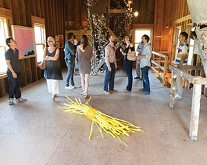 """From the Wassaic Project 2013 summer exhibition """"Homeward Found"""" preview party held on June 15. In the foreground, Tora Lopez's Two Cheers For The Bundle Of Sticks Metaphor. In the background, the ivy wrapped around the wooden structure is Gi"""