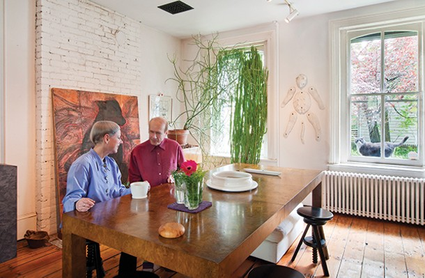 Jan Harrison and Alan Baer in their dining room, with a feline named Sox in the window.