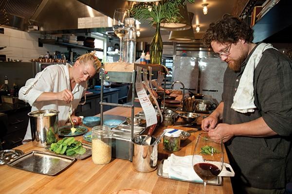 Jori Jayne Emde pouring hollandaise onto aspargus. Zak Pelaccio prepping greens.