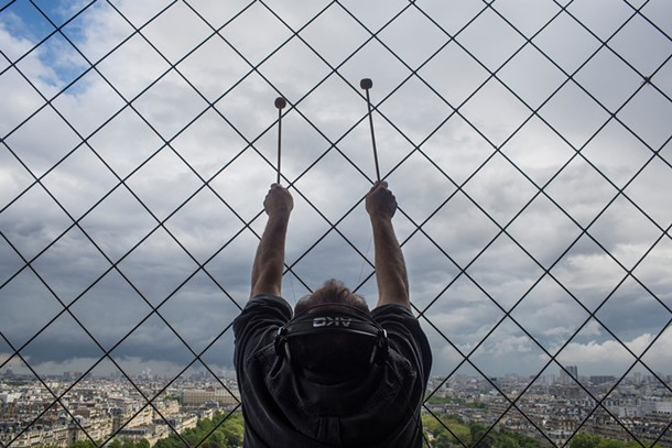 Joseph Bertolozzi creating and recording sounds from the Eiffel Tower.