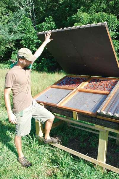 Ken Greene with the solar dehydrator built by partner Doug Muller. - LARRY DECKER