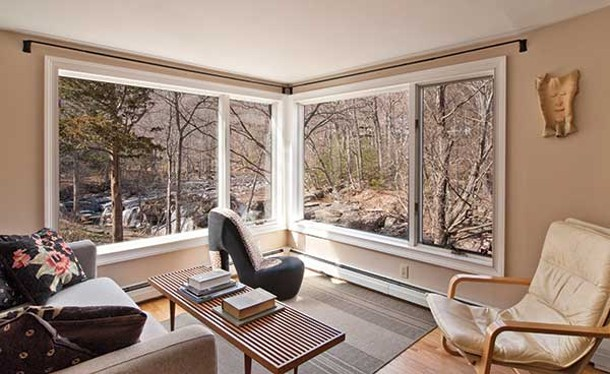 """Living room with view of the falls. Note the giant shoe. Malkin once owned """"Think Big!,"""" retail store in SoHo specializing in oversized versions of classic American ephemera."""