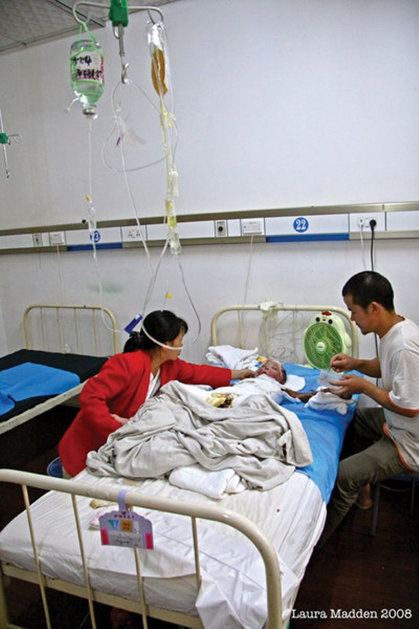 Luo Wenlong, suffering from severe burns over 75 percent of his body, is attended by his parents at a hospital in Hunan Province. The American NGO Handreach donated funding to pay for skin grafting and other treatments for the young boy. - LAURA MADDEN