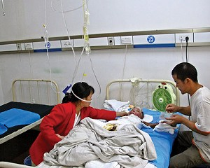 Luo Wenlong, suffering from severe burns over 75 percent of his body, is attended by his parents at a hospital in Hunan Province. The American NGO Handreach donated funding to pay for skin grafting and other treatments for the young boy.