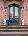Michael Green on the front steps with granite lions that belonged to his mother.