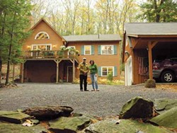 Peter and Elsje Brandt in front of their timber frame home in Woodstock. - PETER BRANDT