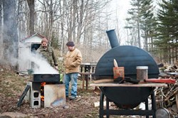 Peter Barrett and Danny Blume watch over the boiling sap; in the foreground, ribs smoke on the smoker. - JENNIFER MAY