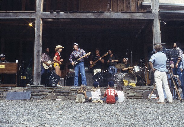 """RCO Picnic Rehersal, Summer 1977 - """"Amy watching her dad rehearse. The entire crew at the barn was gearing up for a big summer picnic Levon was throwing for RCA records. On stage from the far left is Mac Rebennack [aka Dr. John], Steve Cropper, Elizabeth Barraclough, Fred Carter, Jr., Donald 'Duck' Dunn, Paul Butterfield, and Levon. I was charmed by the sight of this all-star band playing their hearts out for an audience of Amy and her friends."""""""