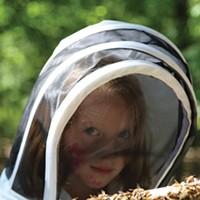 Hudson Valley Bee Supply Ruby, the daughter of bee-tender Katie Benevento, helps open a beehive at Hudson Valley Bee Supply Peter Barrett