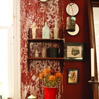 The Wrong Turn to the Right Place The kitchen's deep crimson walls richly offsets the art and simple household goods on display.