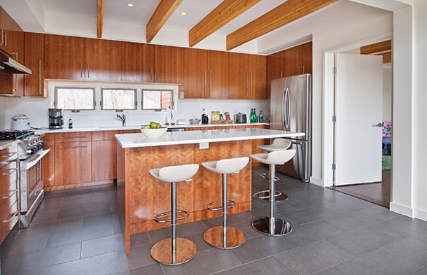 The modern kitchen is open to the dining area and great room, - but separated by the island with its eating area.