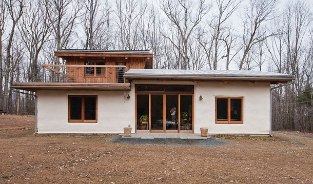 The southern-facing portion of the house with second-floor deck off master bedroom. As finances allow, the couple will expand the bluestone patio and add permaculture. - DEBORAH DEGRAFFENREID