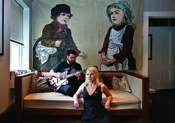Eddie Mullins and Janet Hicks in their living room, with art by Derek Erdman. - DEBORAH DEGRAFFENREID
