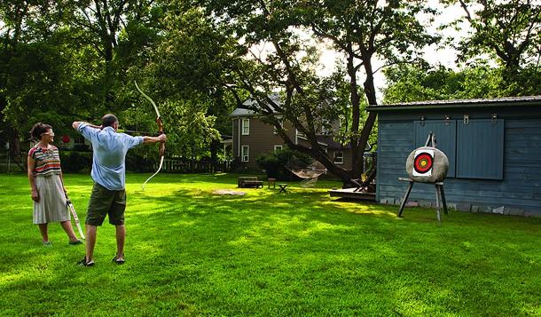 Christina Osburn and Paul O'Connor practicing archery in their backyard. - DEBORAH DEGRAFFENREID