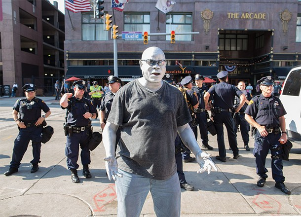 An Afro-American street performer in white face was amazed by a police presence that outnumbered demonstrators four to one. - FRANK SPINELLI
