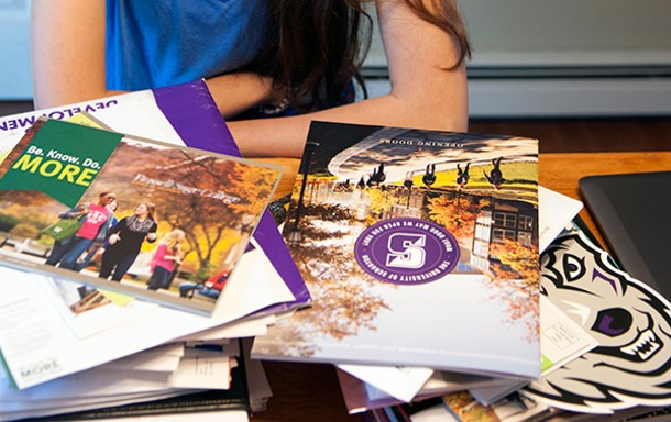 Kate LaValle surrounded by the - materials colleges sent her.