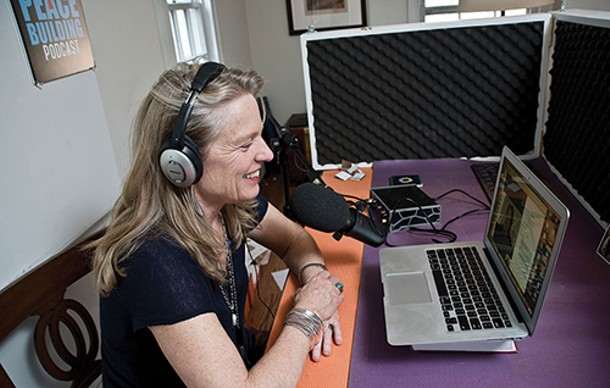 "Coleman in her ""do-jo"" (industry lingo for a sound proof booth) set up in her office.  The Peace Building Broadcast features interviews with coaches, mediators, and all types of negotiators involved in peace-buildling initiatives across the globe. In the past few years, Coleman has become especially interested in ""bringing the feminine into the field of international relations."" - DEBORAH DEGRAFFENREID"
