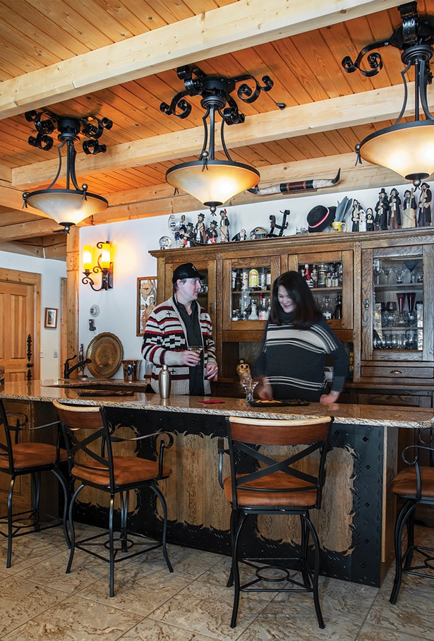 Jack Laroux and his wife, Dr. Christina Koizumi, enjoy a drink in the home's Zakopane bar decorated with handiworks collected from Podhale. Avid skiers and snowboarders, the two met on the slopes at nearby Hunter Mountain. - PHOTO BY DEBORAH DEGRAFFENREID