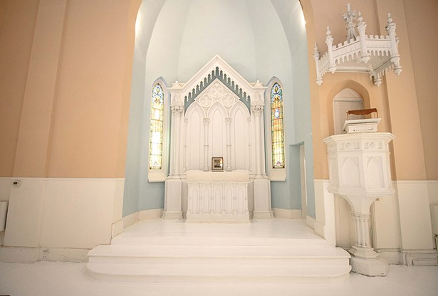 """In redesigning the space Bokaer left the church's original sanctuary and pulpit intact. """"I wanted - to keep everything very respectfully as it was,"""" Bokaer says. With original stained glass windows on either side, the gothic style reredos—the carved centerpiece directly behind the altar—features columns topped with busts of St. Matthew. The crowned pulpit occasionally doubles as a DJ booth. - PHOTO BY SETH DAVIS"""