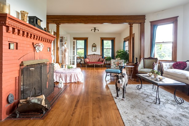 """The first-floor living room features the original red brick fireplace and is decorated with Raimondo's collection of eclectic antiques and vintage fabrics. """"I always wanted a stone house,"""" she says. """"My grandfather built a stone - house in White Plains; but most stone houses have low - ceilings. I love how the ceilings here are so high."""" - PHOTO BY WINONA BARTON-BALLENTINE"""
