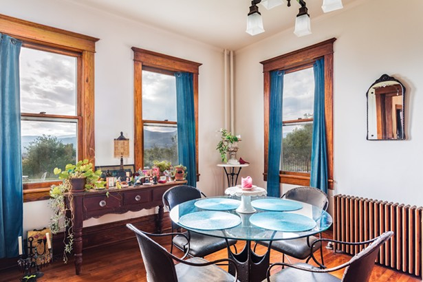 The first-floor dining room features an original cast iron radiator and updated light - fixtures. Raimondo bought the medieval style iron and glass table from Pier 1 and the French Provincial style sideboard from an antiques store in Chelsea. - PHOTO BY WINONA BARTON-BALLENTINE