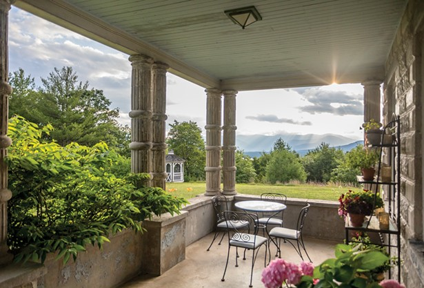 """The covered stone front porch runs the width of the house. """"This is the perfect place to sit,"""" Raimondo says of the porch. """"It's especially beautiful when it rains."""" - PHOTO BY WINONA BARTON-BALLENTINE"""