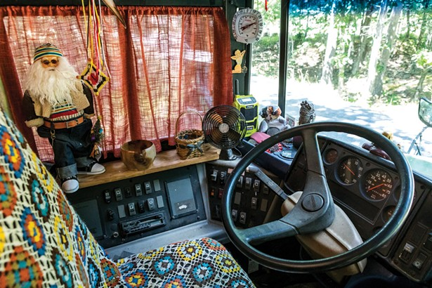 """The front seat of Julie Snyder's bus, which she's named Brigantia. The bus is drivable and Snyder has taken it all over the northeast. """"It fits in exactly two parking spaces, end to end,"""" she explains. - PHOTO BY WINONA BARTON-BALLENTINE"""