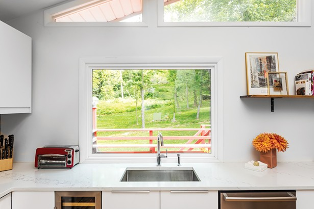 """The renovated kitchen looks out through windows and sliders to the lawn and woods behind the house. The couple is divided over which room in the house is the best place to sit. """"Each area offers a different experience,"""" says Schultz. """" Aaron loves the dining room in back because it's nested and you can hear birds in the nearby trees, but still see the views further away. I love the front because it's closer to the river."""" - PHOTO BY WINONA BARTON-BALLENTINE"""