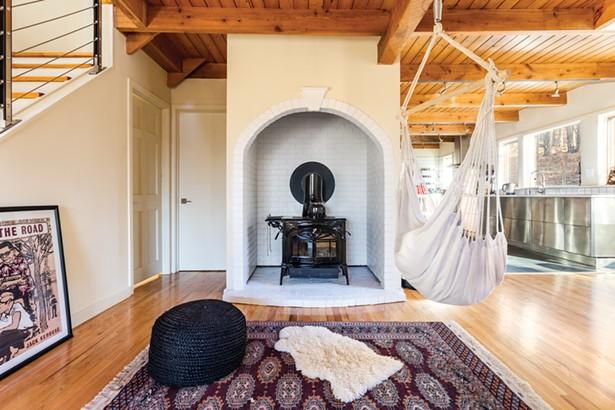 The home's arched brick alcove and woodstove are the final remnants of the home's - original southwestern-inspired interior. Throughout the home, a mix of Oriental area rugs line the wood plank floors. Some were bought while traveling in Istanbul and some were bought at Anatolia in Woodstock. - PHOTOS BY WINONA BARTON-BALLENTINE