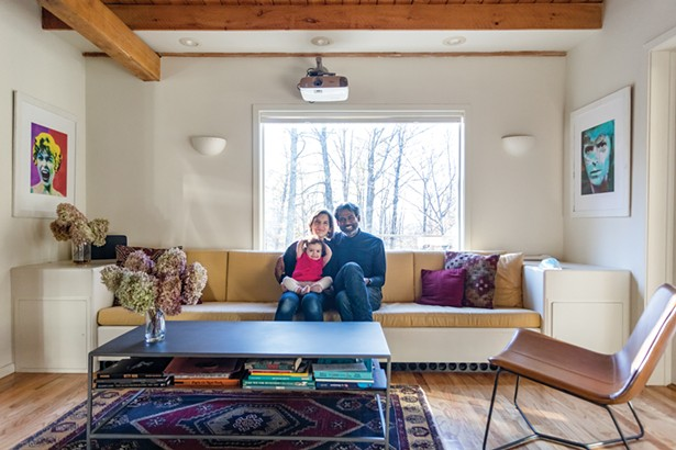 """Duflo, Kant, and their daughter Ila in the home's living room. They kept the home's built-in sofa, but completely reworked the rest of the interior. """"Our goal was to create open spaces with furniture that was simple and had straight lines, mostly mid-century,"""" says Kant. """"Then we added splashes of art and color—mixing roadside pop art with antiques or pieces from our travels."""" - PHOTOS BY WINONA BARTON-BALLENTINE"""