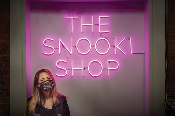 """Stephanie Rodrigues, manager of the Snooki Shop, in front of the selfie background neon sign. Nicole Polizzi, aka Snooki, of """"Jersey - Shore"""" fame, grew up nearby in Marlboro. The Snooki Shop opened on Main Street last fall. - DAVID MCINTYRE"""
