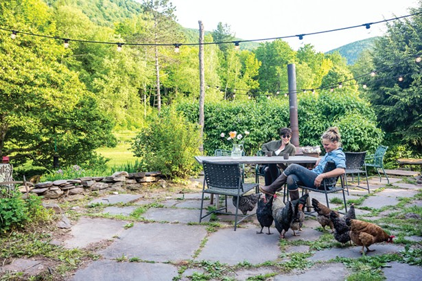 """Anne Hall and her partner Kate Steciw enjoy some down time between tending to their creative work and flower gardens (and the resident flock of chickens). """"When the temperature warms up, we spend most of our time on the back patio surrounded by a blooming magnolia tree, red-winged blackbird males stalking their territory, chickadees flitting, and the mountains, distant but ever present."""" - WINONA BARTON-BALLENTINE"""