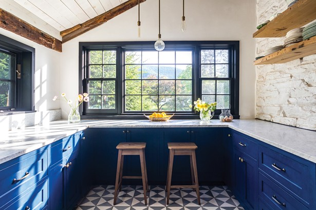 The home's original kitchen was completely gutted and rebuilt from the studs to the roof. Hall kept - the original wood ceiling beams, but lightened the space with a white wash of paint to the ceilings and walls. Marble countertops and cobalt blue cabinets modernize the space and black-and-white Moroccan-style tiles accentuate the floor. - WINONA BARTON-BALLENTINE