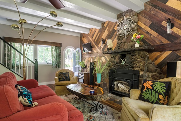 """The home's living room was completely redesigned and rebuilt by Facci and Gironda in 2015. They rebuilt the walls, refinished the floors, painted, and added the fireplace insert.The space is decorated with an eclectic mix of Facci's craft work. """"I'm an avid crafter andmy mind is always looking for things I can make,"""" she - explains. Facci created faux birch logs in the fireplace out of old pizza boxes. She created the fireplace's centerpiece mirror out of - garden sticks painted black and white to look like birch - WINONA BARTON BALLENTINE"""