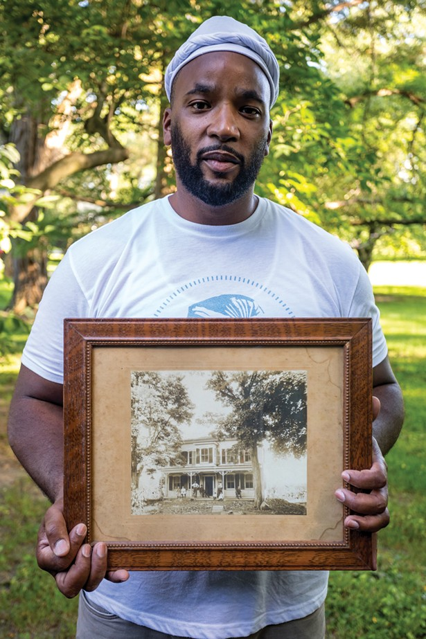 Jackson holds a photo of the house from the 19th century. Before he and his wife bought the home in 2015, it had been passed down from the original Dutch settlers through their descendants. The house's original windows are intact but the covered porch was removed long ago. - WINONA BARTON-BALLENTINE