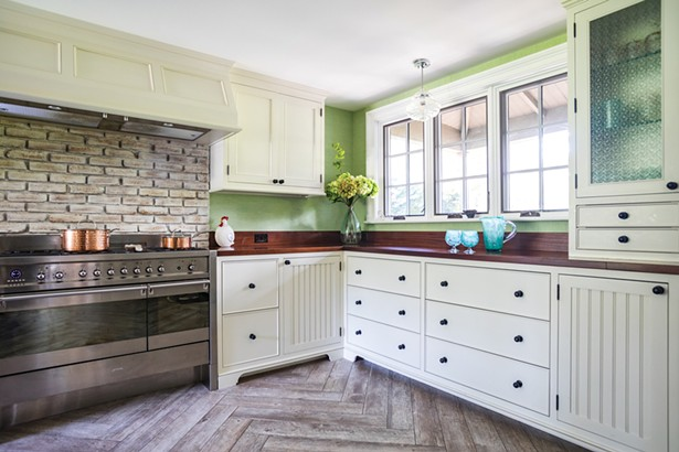 """The house's original woodstove (it's now in his carpentry shop) was replaced with a stainless steel six-burner stove. The kitchen is finished in African ribbon-striped sapele wood on the counters and pantry cabinets. Jackson added the south-facing window over the counter. """"It really brings the outside inside,"""" he says. - WINONA BARTON-BALLENTINE"""
