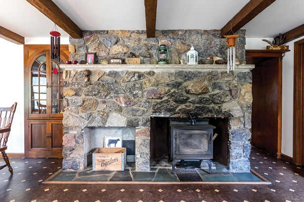 """The dining room features the original bluestone fireplace with a woodstove. The home has two other woodstoves which can heat the house throughout the winter. """"I cut a lot of wood during the summers,"""" says Zimmerman. """"In winter, the home has a nice homey feeling inside."""" - WINONA BARTON-BALLENTINE"""