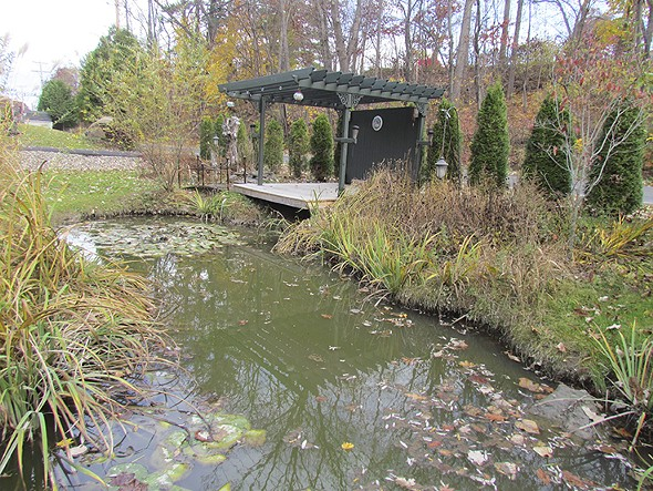 Residents of the home and their families can rest on a bench next to a peaceful pond. - CIRCLE OF FRIENDS