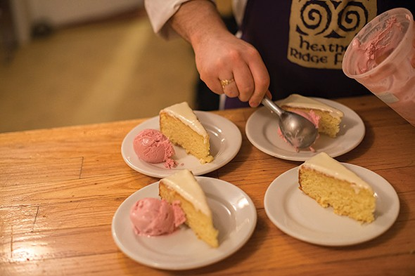 Adding damson plum sorbet to plates of white chocolate lemon cake - JIM MAXIMOWICZ