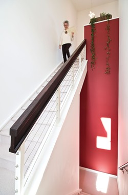 "Meyer-Fitzsimmons in the stairwell leading to her home office. She began her research for her Master's degree—which was to become her book Deep Living—in the `90s and found she really enjoyed the writing process. ""It's sort of like constructing a puzzle out of pieces of information."" - DEBORAH DEGRAFFENREID"