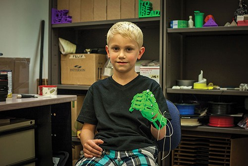 """Joseph Gilbert shows off his prosthetic """"robo hand"""" that was 3D printed at SUNY New Paltz's Additive Manufacturing Center. - ROY GUMPEL"""